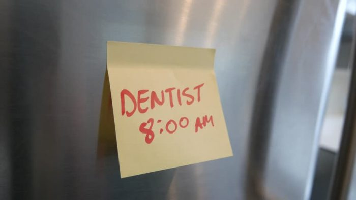 Yellow sticky note on a stainless steel fridge written ''Dentist 8:00 AM''
