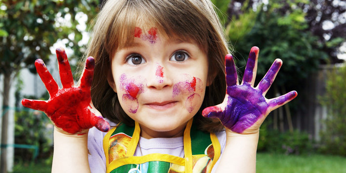 Cute girl with paint on her hands and face