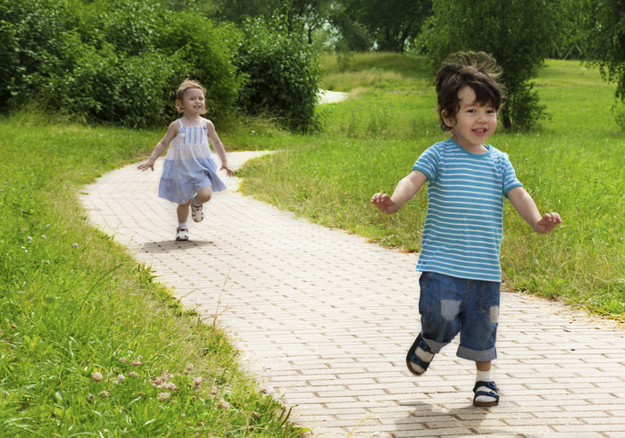 Toddlers running down a path.